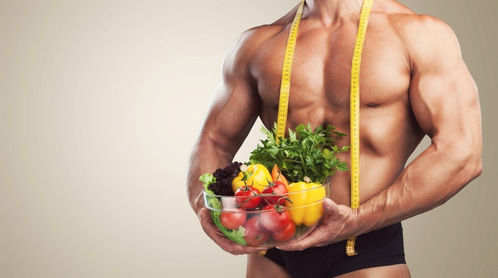 man-with-muscles-standing-with-food